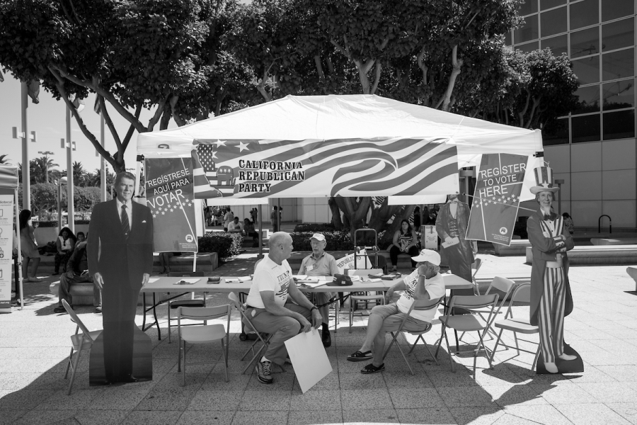 Volunteers sitting in chairs at an otherwise empty booth, large Ronald Reagan cutout on left