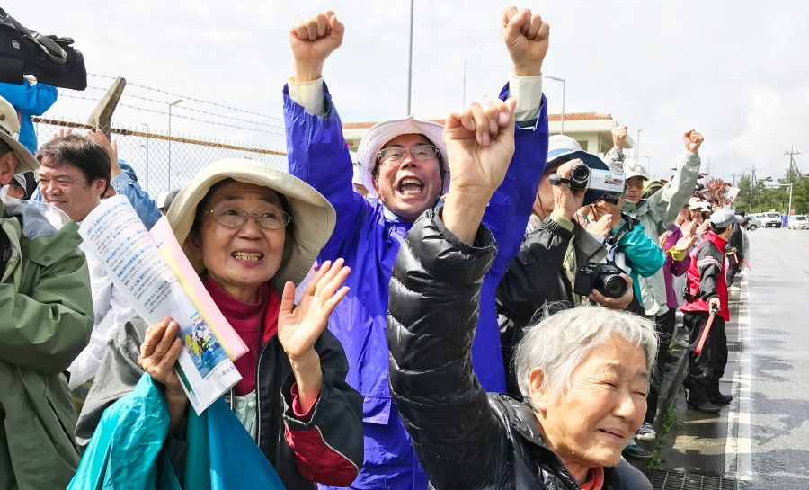 Etsuko Urashima stands left among several oether protesters — arms raised — in Henoko, Japan