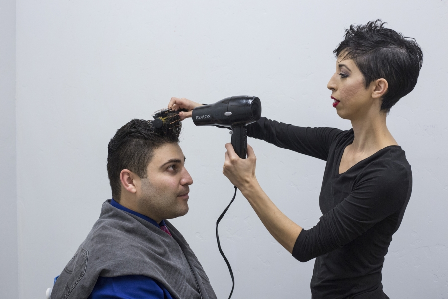 Omar's wife, Jasmín, helps him fix his hair before their performance