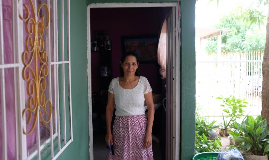Ana Luz Ortega stands in the doorway of her home in the City of Women.