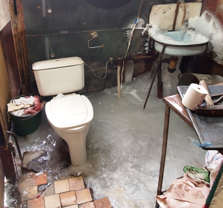 Winters in the container homes are especially tough: notice the solid ice on the floor and sink.