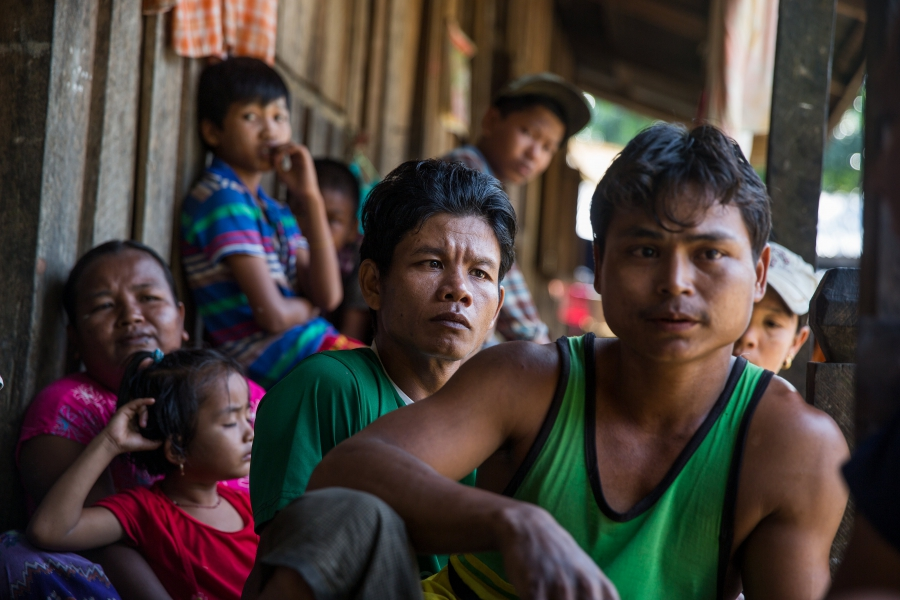 Workers and their families, including Zaw Myo Htike (foreground in green sleeveless shirt), gather on their porches at a small village where migrant workers for Supowin Palm Oil live outside Kawthaung, Myanmar, Nov. 14, 2016. Many workers on this plantati