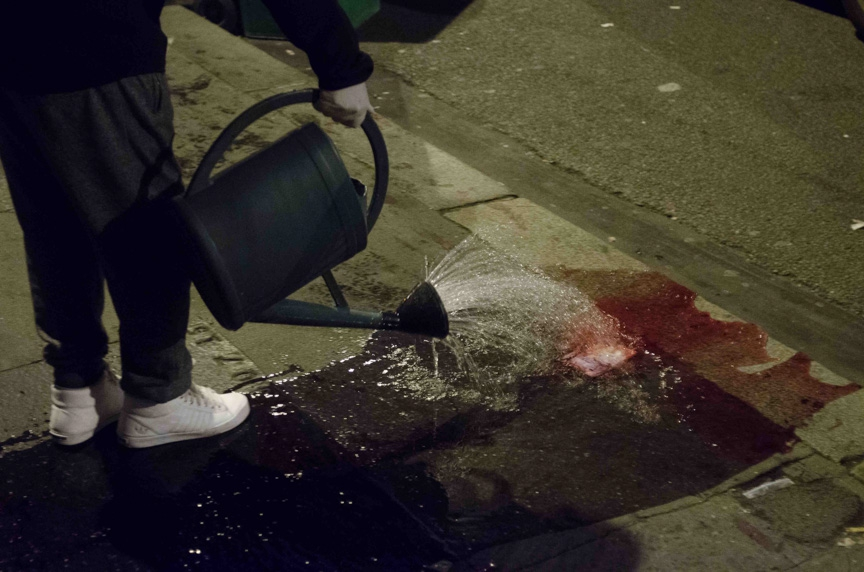A resident washes away blood from Rue Oberkampf in the 11th district Friday night.