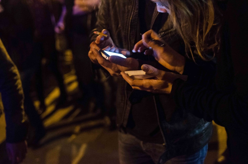 Bystanders and victims write down phone numbers to make calls near the Bataclan concert hall in Paris on Friday night.