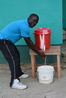 Pastor Peter Flomo demonstrates faucet bucket with bleach solution