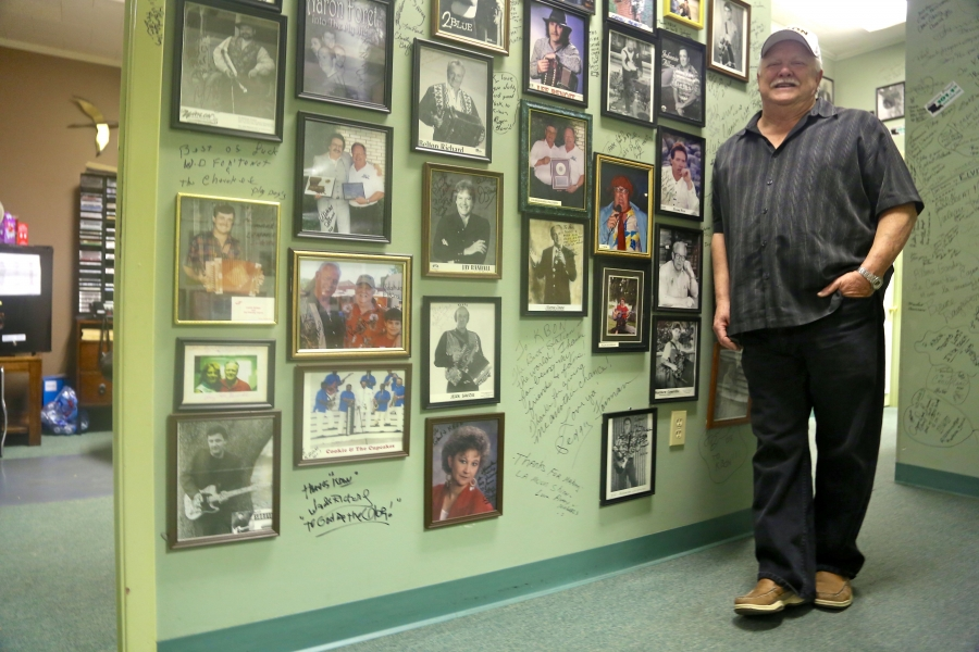 "Paul Marx, owner of KBON radio station in Eunice, LA, stands near a collection of autographed photos and a wall covered in signatures. His station mostly plays music by Louisiana musicians, including Jamie Bergeron & The Kickin' Cajuns, whose song ""Regist"