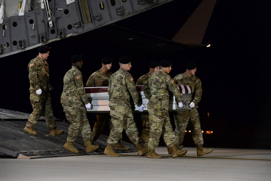 A US Army carry team transfers the remains of Army Staff Sgt. Dustin Wright moving the casket off of an aircraft.