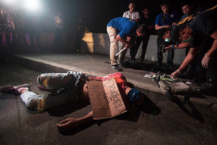 "A victim of summary execution, with packing tape wrapped around his head and a sign on his chest that reads, ""I am a Chinese drug lord,"" found along Road 10 in Manila."