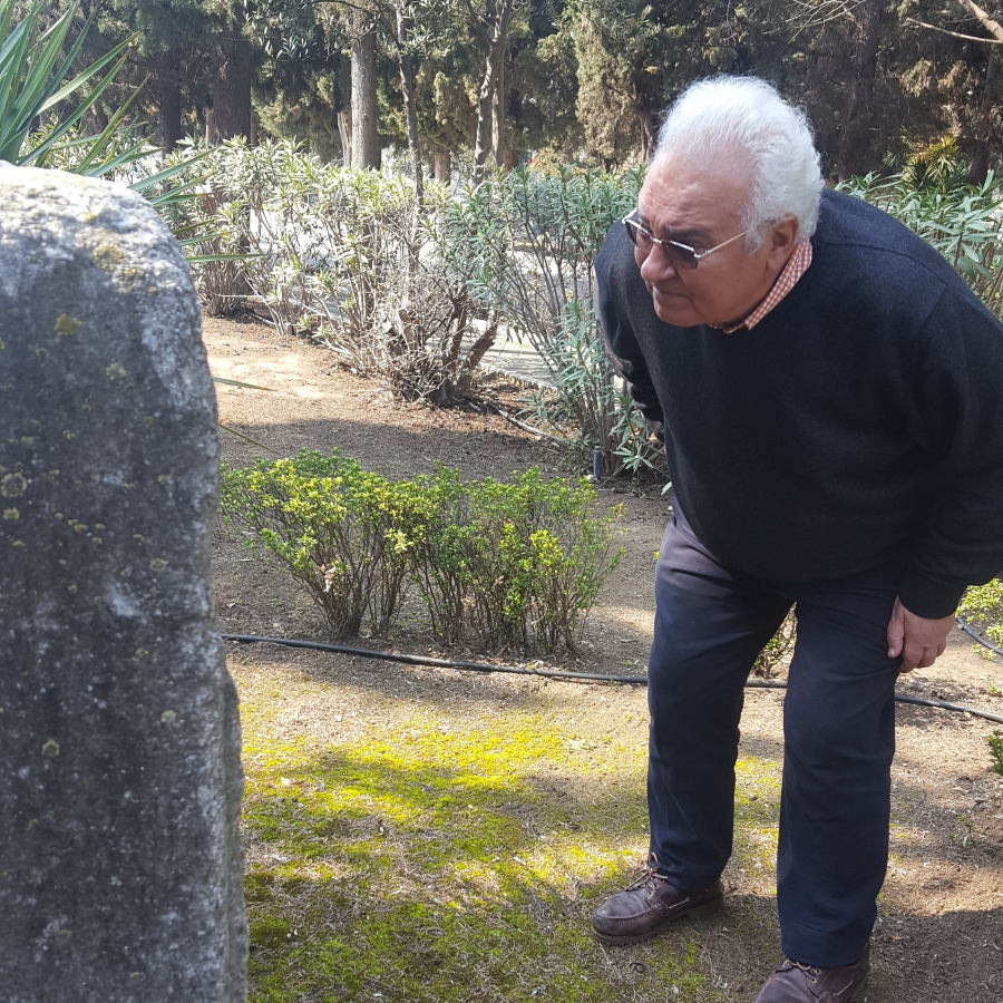 Jacky Benmayor stoops down to get a better look at an old tombstone at the newer Jewish cemetery.