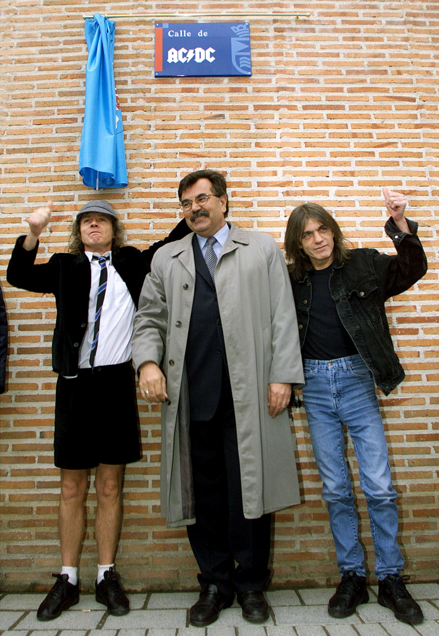 Angus (L) and Malcolm (R) Young, founder members of Australian Heavy Metal band AC/DC, flank Jose Luis Perez, mayor of the Madrid district of Leganes, following the inauguration of a new street with the group's name March 22.