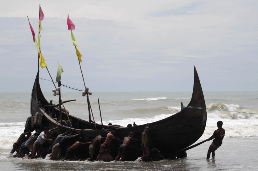 Rohingya fishermen pull a boat near a refugee camp in Cox's Bazar, Aug. 19, 2011.