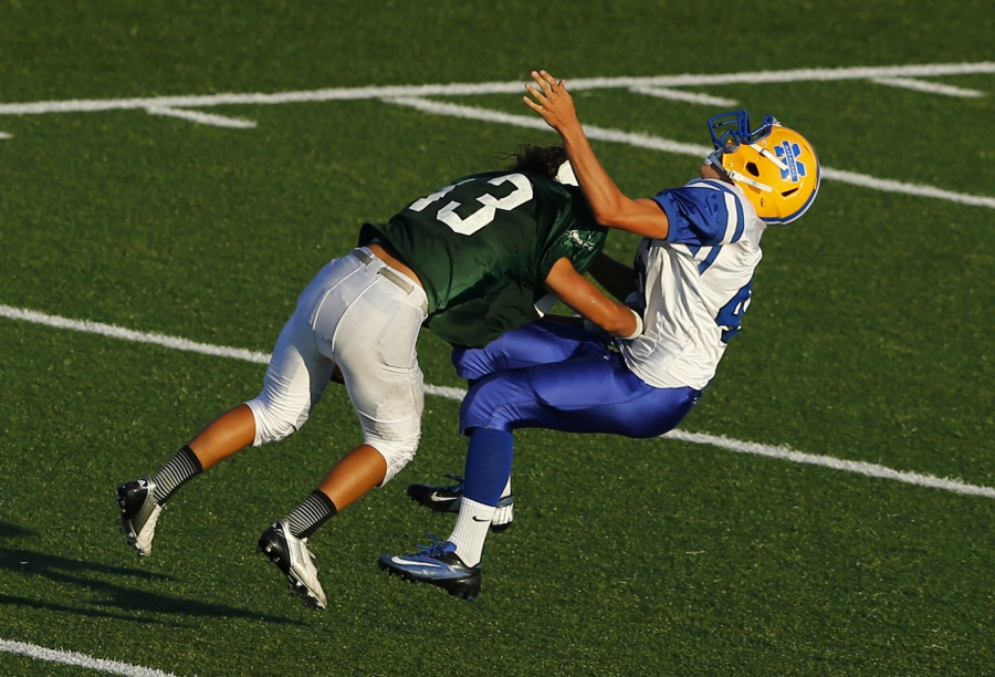 A Mira Mesa Junior Varsity high school football player trying to punt the ball is hit to the turf by an Oceanside Pirates player during their game in Oceanside, California September 14, 2012.