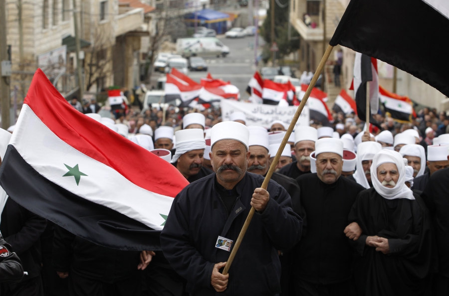 Members of the Druze community hold Syrian flags during a rally in the Druze village of Majdal Shams in the Golan Heights, Feb. 14, 2013.