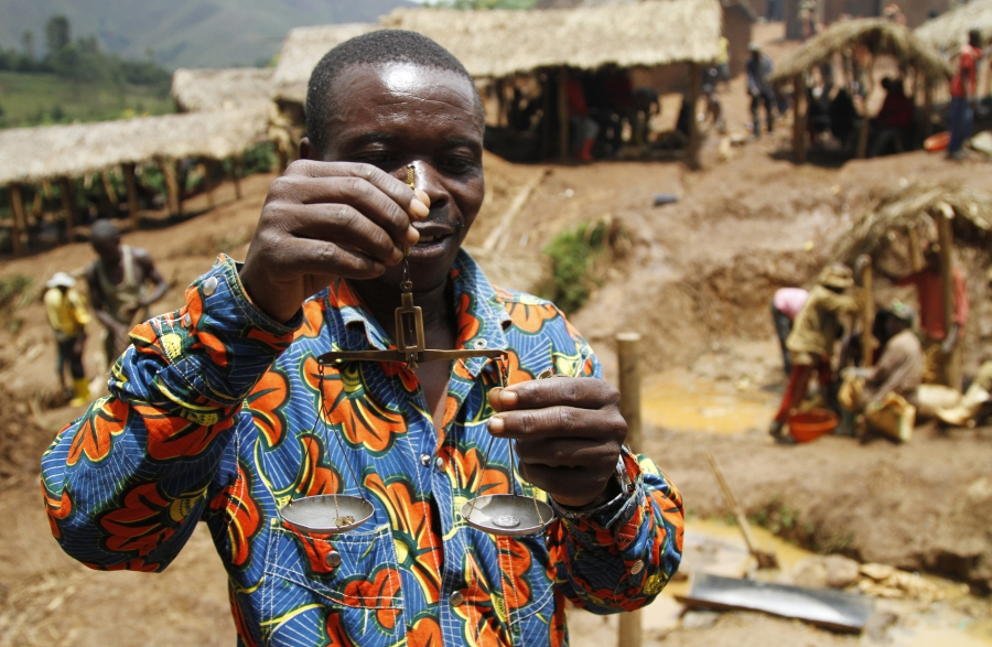A trader weighs gold nuggets at an illegal mine-pit in Walungu territory of South Kivu province near Bukavu, DRC, April 5, 2014.