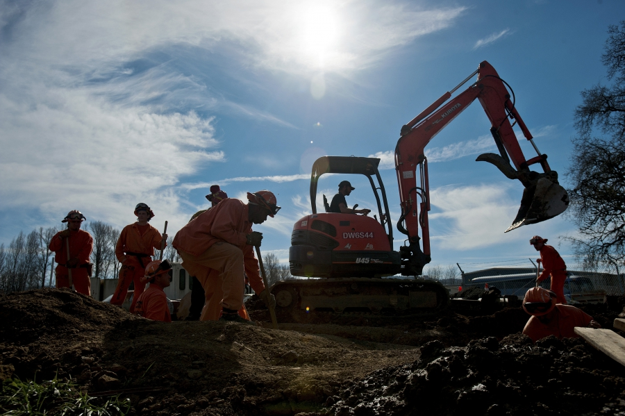 Prison laborers and an excavator operator help construct an emergency pipeline to increase supplies of potable water in Willits, California February 25, 2014.