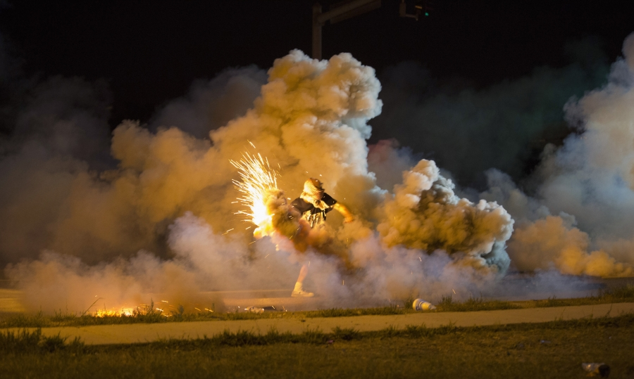 A protester throws back a smoke bomb while clashing with police in Ferguson, Missouri, on August 13, 2014.