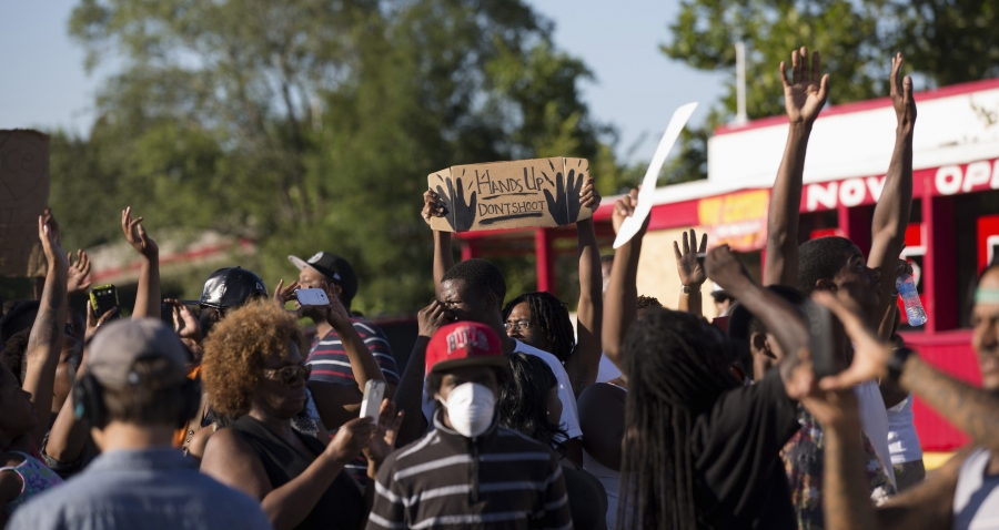 Demonstrators raise their hands while protesting the shooting death of teenager Michael Brown in Ferguson, Missouri, on August 13, 2014.