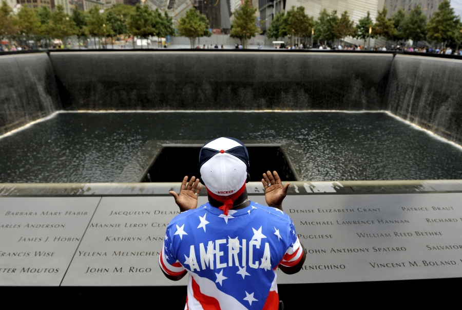 Man praying in front of memorial