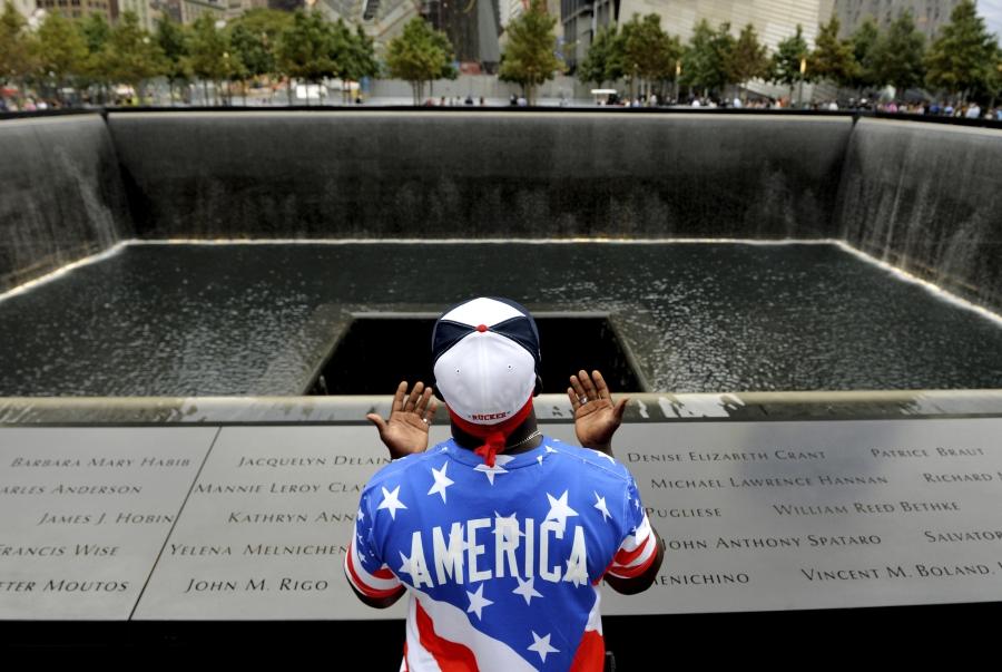 Man praying in front of memorial