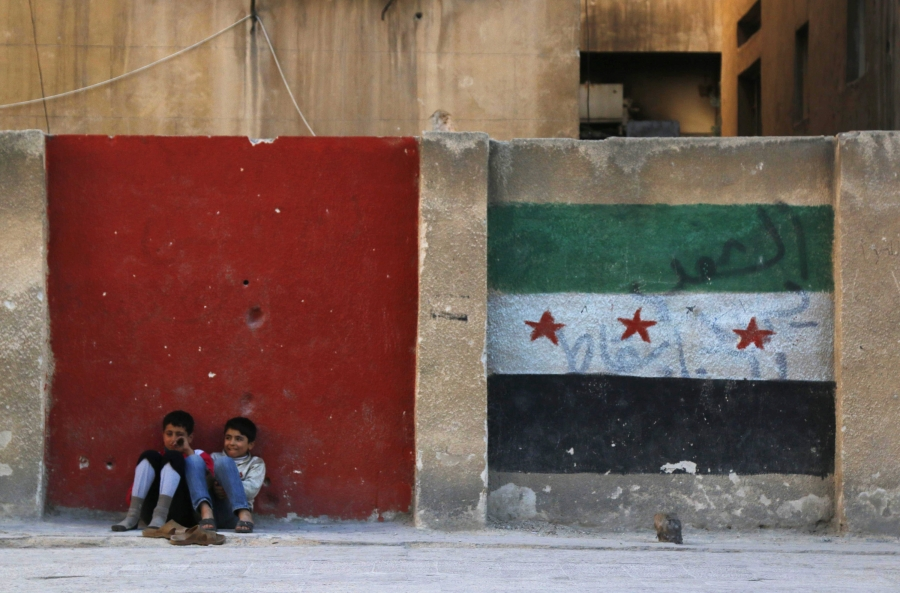 Children sit next to a wall painted with an opposition flag along a street in Aleppo on November 8, 2014.