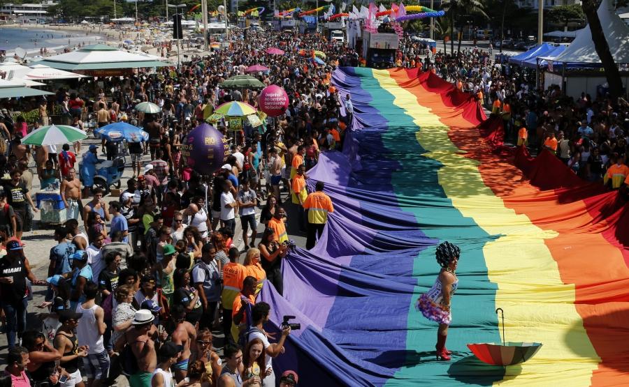 A participant performs on a giant rainbow flag during a Gay Pride Parade at Copacabana beach in Rio de Janeiro on Nov. 16, 2014.