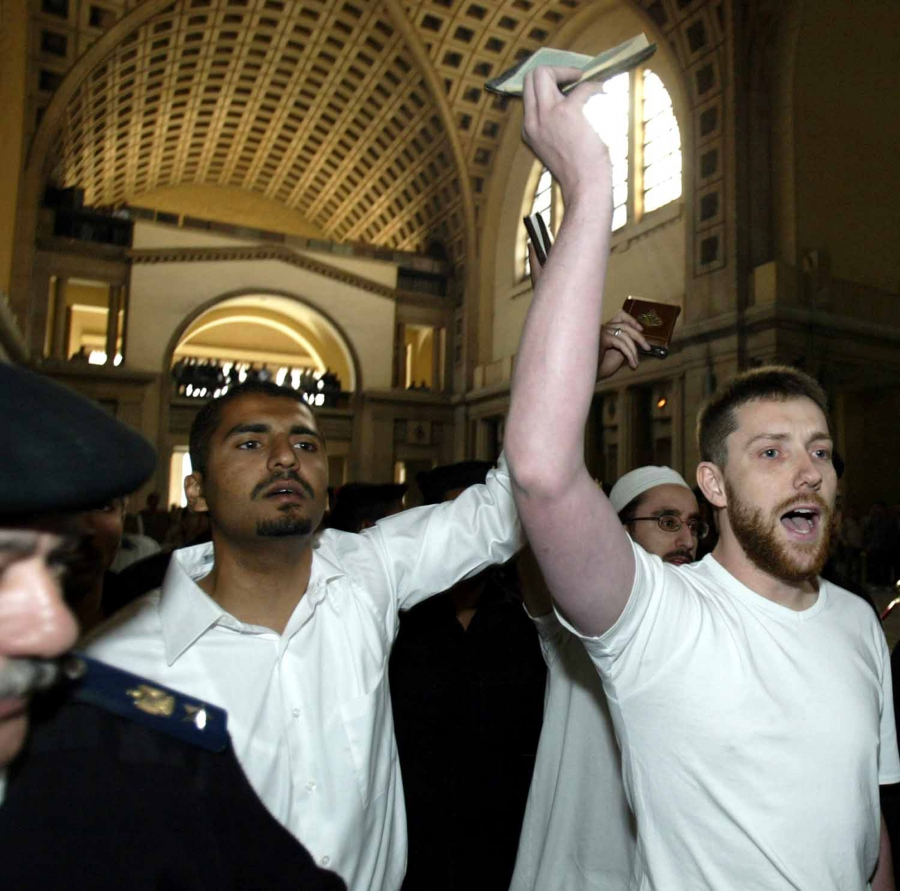 Maajid Nawaz (left) and fellow British citizen Ian Nisbet hold up copies of the holy Quran as they are led to court in Cairo, Egypt in March 2004. Nawaz and Nisbet were among a group of 26 people arrested in Egypt and sentenced to jail time for promoting