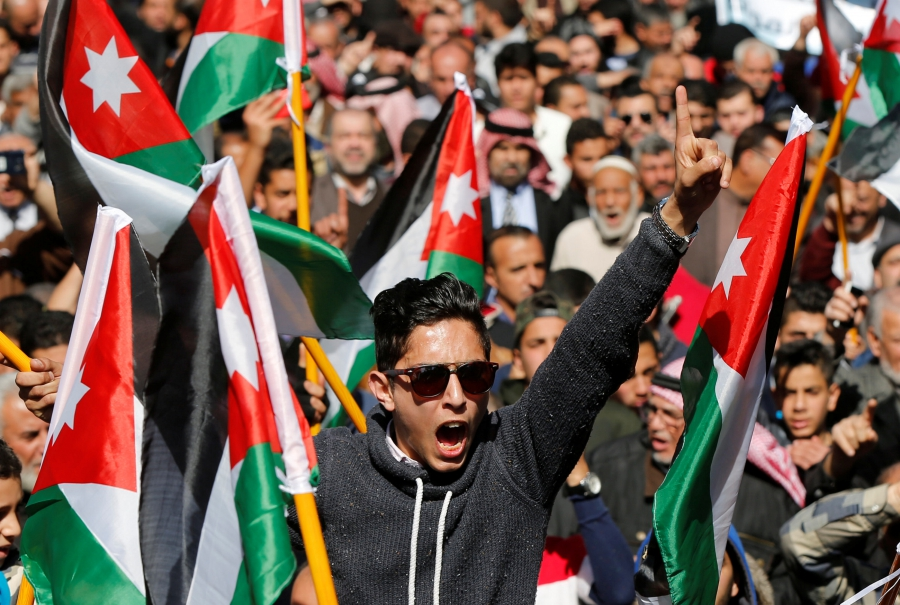Demonstrators hold Jordanian national flags and chant slogans during a protest against rising prices and the imposition of more taxes, after the Friday prayer in Amman, Jordan, Feb. 24, 2017.
