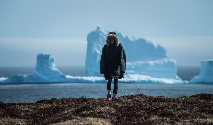 A resident views the first iceberg of the season as it passes the South Shore near Ferryland Newfoundland, Canada.