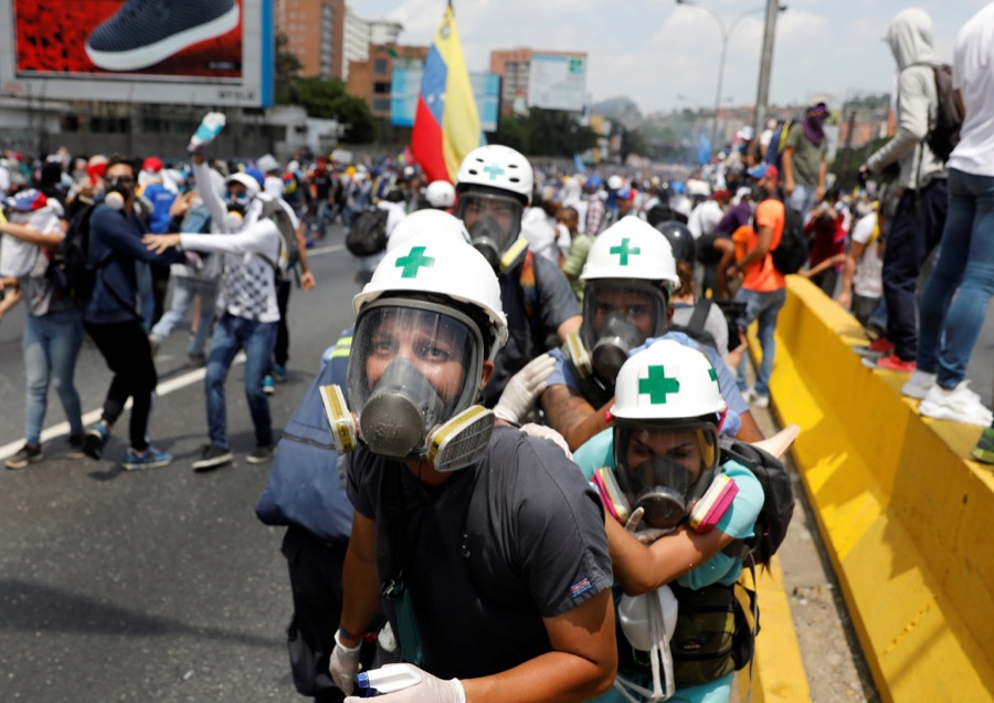 Volunteer members of a primary care response team huddle together during clashes with security forces at a rally against Venezuela's President Nicolas Maduro in Caracas, Venezuela