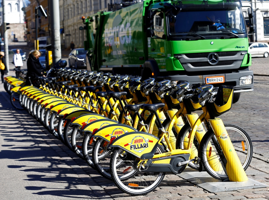 A vehicle passes near a dock for Helsinki's bike-sharing system, on May 3, 2017.