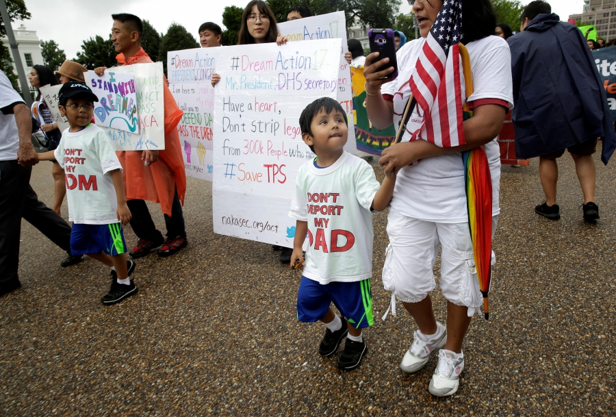 Boys wearing shirts calling for their parents not to be deported march during a rally by immigration activists CASA and United We Dream