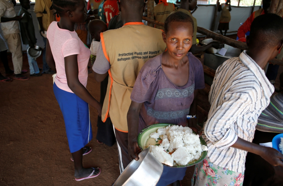 A South Sudanese woman collects a meal in Omugo refugee settlement camp in northern Uganda on Aug. 23, 2017.