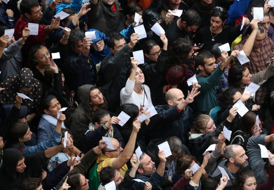 Voters hold up ballot sheets outside a polling station for the banned independence referendum in Barcelona, Spain, on Oct. 1, 2017.