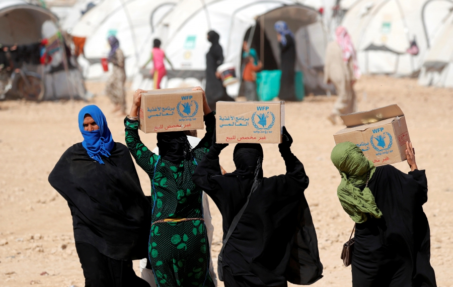 People displaced by the Syrian civil war carry boxes of food aid distributed by the UN's World Food Program at a refugee camp in Ain Issa, Syria, Oct. 10, 2017.