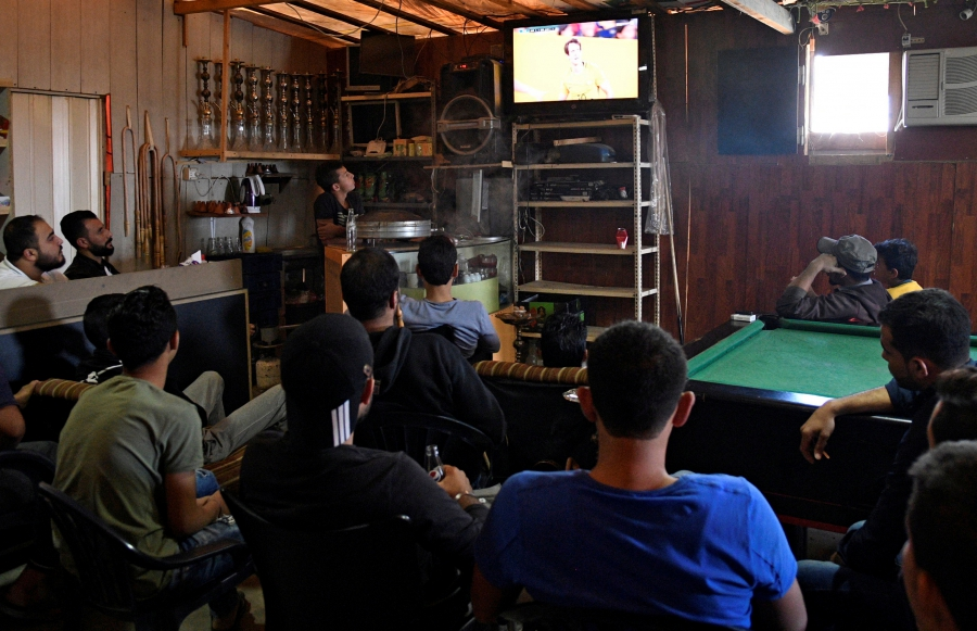 Syrians watch the World Cup 2018 qualifier between Australia and Syria inside a refugee camp in Bar Elias, in the Bekaa Valley, Lebanon, Oct. 10, 2017.