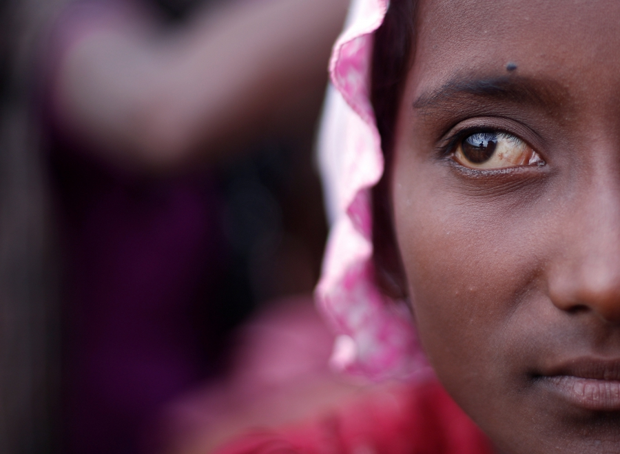 A Rohingya refugee girl waits to be taken to a refugee camp