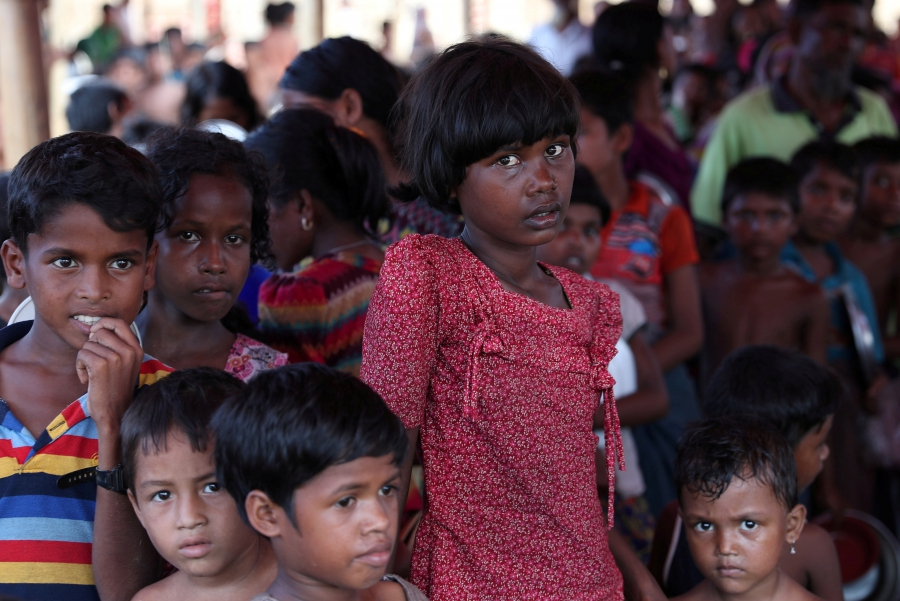 Rohingya refugees wait in a queue to collect food at the Palongkhali makeshift refugee camp in Cox's Bazar