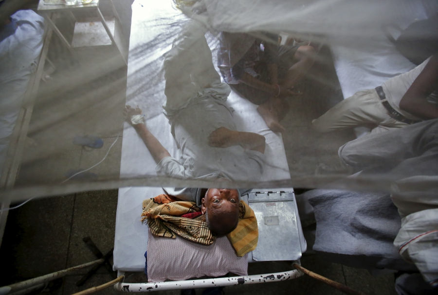 A patient awaits routine check-up as he lies under a mosquito net inside a dengue ward of a government hospital in New Delhi, India, September 18, 2015.