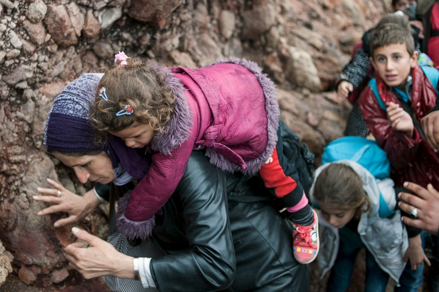 A migrant woman carries her child after arriving at a rocky beach on the Greek island of Lesbos after crossing a part of the Aegean Sea from the Turkish coast to Lesbos.