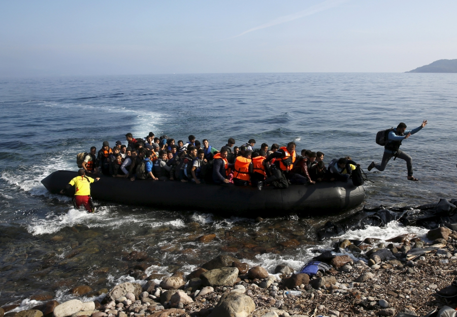 A migrant jumps off an overcrowded raft onto a beach on the Greek island of Lesbos, Oct. 19, 2015.