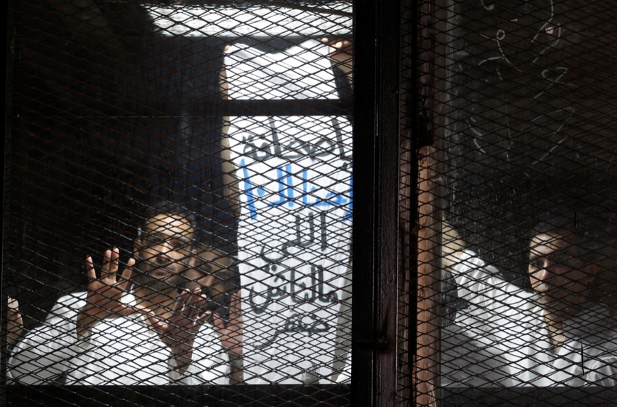 Egyptian journalists behind bars during a court trial outside Cairo