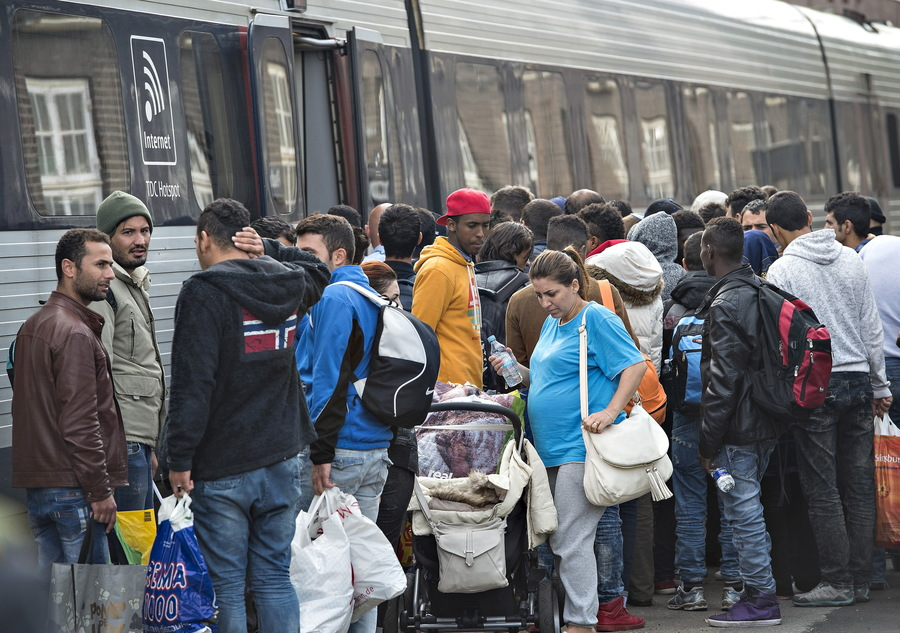 Migrants, mainly from Syria, prepare to board a train headed for Sweden, at Padborg station in southern Denmark, Sept. 10, 2015.