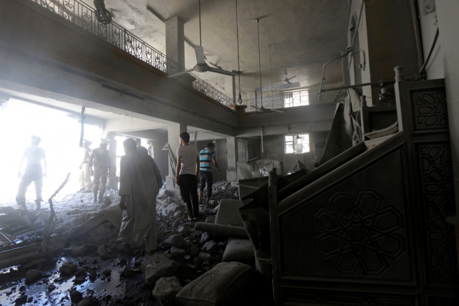 Civil defense members and residents inspect damage inside al-Aqsa mosque after an airstrike on the rebel held Al-Hilwaniyeh neighborhood in Aleppo on July 14.
