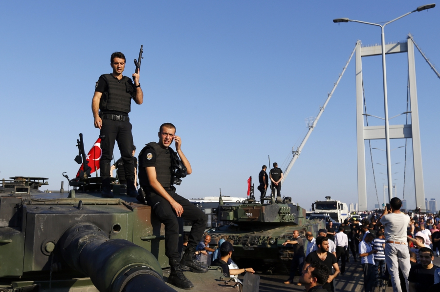Policemen stand atop military armored vehicles after troops involved in the coup surrendered on the Bosphorus Bridge in Istanbul, Turkey, on July 16, 2016.