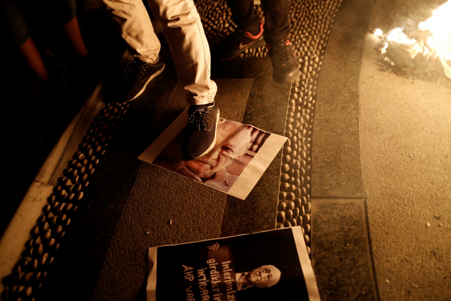 A supporter of Turkish President Tayyip Erdogan steps on a photo of U.S.-based cleric Fethullah Gulen during a pro-government demonstration on Taksim Square in Istanbul, Turkey, July 18, 2016. REUTERS/Alkis Konstantinidis