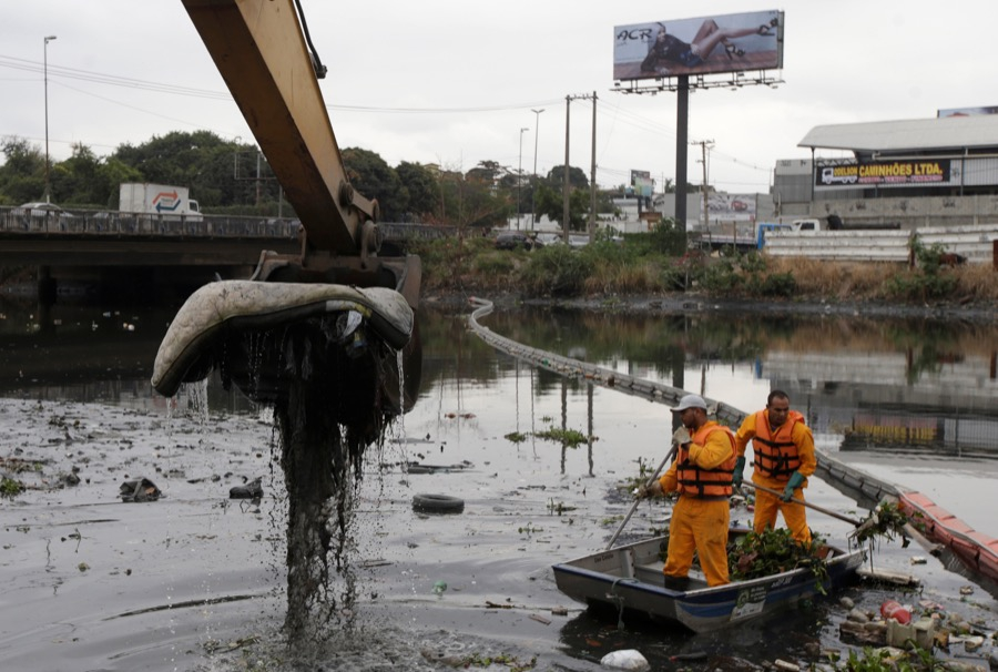 Workers clean up the garbage next to an eco-barrier at Meriti River, which flows into Guanabara Bay, in Duque de Caxias, near Rio de Janeiro, Brazil, on July 20.