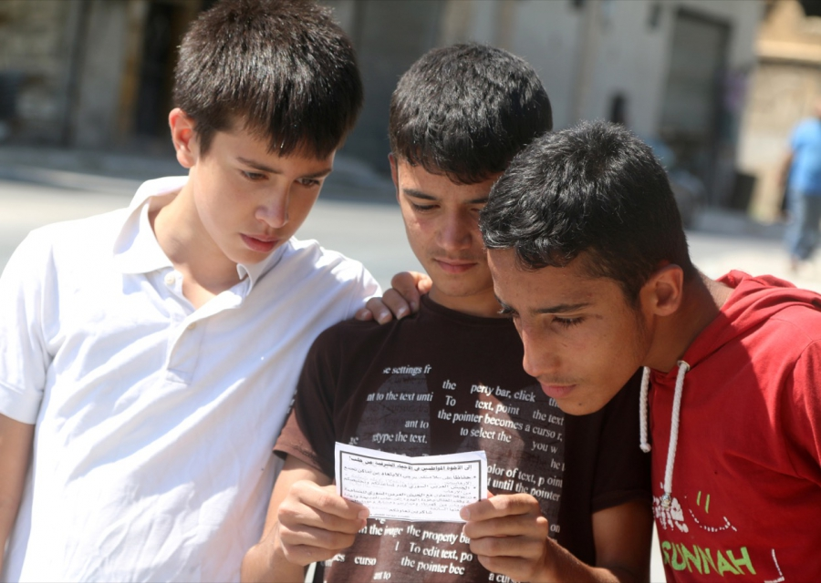 Boys read one of the informational leaflets dropped by the Syrian army over opposition-held Aleppo districts.