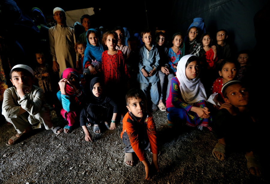 Afghan refugee children, returning from Pakistan, watch a short video about mine safety and explosives awareness at a UNHCR registration center in Kabul, Afghanistan, Sept. 27, 2016.