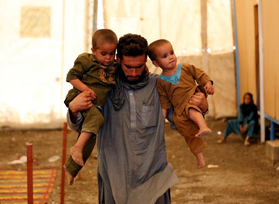 An Afghan refugee holds his children after arriving at a UNHCR registration center in Kabul, Afghanistan, Sept. 27, 2016.