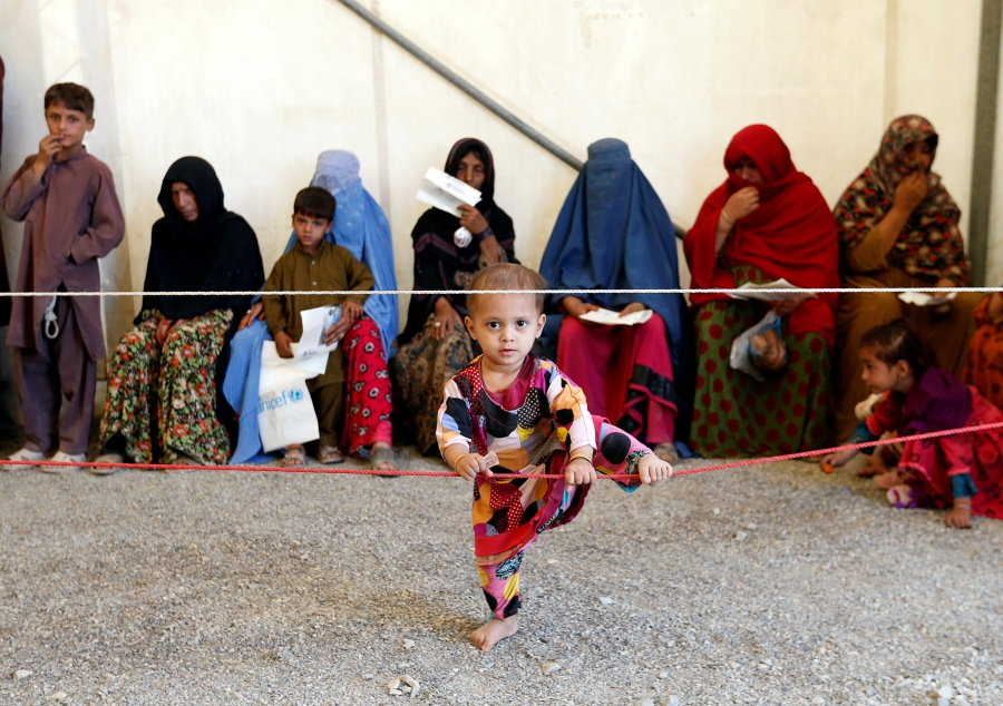 Afghan women sit with their children after arriving at a UNHCR registration center in Kabul, Afghanistan, Sept. 27, 2016.